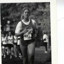 """Image of 1992 Cross Country Running 3 - """"1992 - X-Country""""  A young woman with blonde hair runs ahead of the pack in her """"EASTERN OREGON"""" cross country uniform."""
