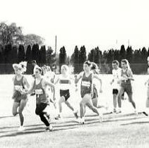 """Image of 1992 Cross Country Running 4 - """"1992 - X-Country""""  Running with the pack are a number of  """"EASTERN OREGON,"""" uniform wearing, cross country team members.  This looks like a competition with another school."""