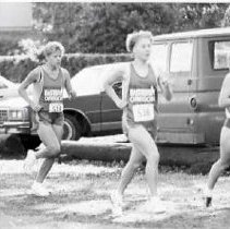 """Image of 1992 Cross Country Running 5 - """"1992 - X-Country""""  Running by several vehicles, including and old van are three young women in """"EASTERN OREGON"""" cross country uniforms.  Two men at the left of the picture watch the upcoming runners."""