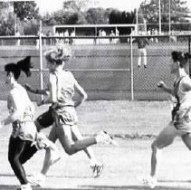 """Image of 1992 Cross Country Running 6 - """"1992 - X-Country""""  Wearing their """"EASTERN OREGON"""" cross country uniforms, several young women run along the outer perimeter of the baseball field where a game is in progress.  At the very top right, fans are watching the game from the bleachers"""