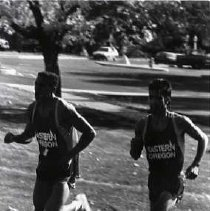 """Image of 1992 Cross Country Running 7 - """"1992 - X-Country""""  Wearing their """"EASTERN OREGON"""" cross country uniforms, two young men run on the grass across campus."""