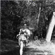 """Image of 1992 Cross Country Running 8 - """"1992 - X-Country""""  Ahead of a number of other runners, an """"EASTERN OREGON"""" cross country team member runs through a forest area."""