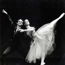 "Image of Ballet, Nutcracker - ""Eugene Ballet Nutcracker""  A couple perform ballet together.  She is wearing a tulle skirt, and is poised on the toe of her right foot.  He is supporting her with his left hand and shoulder, and he's wearing dark tights and long sleeved costuming."