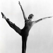 "Image of Ballet & Dance - ""Tandy Beal""  A woman wearing a full leotard with spaghetti straps poses in a dance position.  She is up on the toes of her left foot wtih her right leg and both arms in the air.  Her face looks upward, and  her hair is pulled back in a bun."