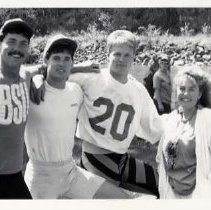 "Image of 90's Raft Race Team 1 - ""Raft Race""  Three athletic young men pose with a young woman during raft race preparations.  The Grande Ronde River and other people are visible in the background."