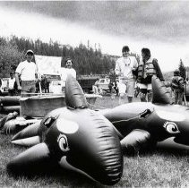 "Image of 90's Raft Race Team 2 - ""Raft Race""  It may not work all that well, but this was creative.  A raft race team has tied two inflatable orcas to the front of a children's wading pool.  Other teams can be seen around their rafts in the background."