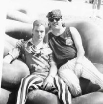 "Image of 90's Raft Race Team 3 - ""Raft Race""  Two young men lounge together on a pile of inner tubes.  Both are wearing kerchiefs on their heads, and vertically striped pants."