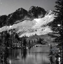 "Image of Oregon, Blue Lake - ""Blue Lake""  With a small amount of snow still on them, the Blue Mountains stand tall above Blue Lake.  There are rocks and evergreens around the lake.  [Also, note the small circular ripple near the bottom left corner.  Curious.]"