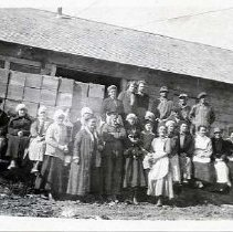 "Image of 1900+/- Oregon, Fruit Workers - ""Wilson's Fruit Workers""  A large group of both men and women pose together on the loading area of an old fruit station.  The building looks like an over-sized wood shed, and there are stacked boxes of fruit behind the workers."