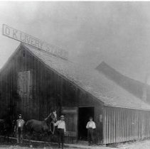 "Image of 1900+/- Oregon, Livery Stable - ""OK Livery Stable""  This is a livery stable where horses were housed and cared for.  There are three men standing out front, two of them with bridled horses."