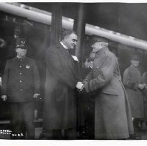 "Image of 1917-33 Portland, Dignitaries 2 - ""Pershing (St.), Mayor of Portland""  Mayor George Luis Baker of Portland, OR, who served from 1917 to 1933, shakes hands with another official.  There is a police officer behind the mayor, and there are numerous other gentlemen standing around what appears to be a train station."