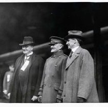 "Image of 1917-33 Portland, Dignitaries 3 - ""Man with ribbon on is Mayor [George Luis] Baker of Portland""  Three gentlemen stand together at what appears to be a train station.  The man on the left is Mayor Baker of Portland, OR who served from 1917 to 1933.  Next to him is a man wearing a double-breasted overcoat and military officer type hat.  The third man is also wearing an overcoat and hat, but they are civilian clothes."