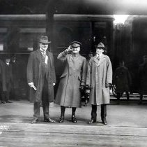 "Image of 1917-33 Portland, Dignitaries 4 - ""Mayor of Portland""  Three gentlemen stand together at what appears to be a train station.  The man on the left is Mayor George Luis Baker of Portland, OR who served from 1917 to 1933.  Next to him is a man wearing a double-breasted overcoat and military officer type hat.  He is kind of half saluting, half waving.  The third man is also wearing an overcoat and hat, but they are civilian clothes.  There is a train in the background with a number of gentlemen standing in front of it."