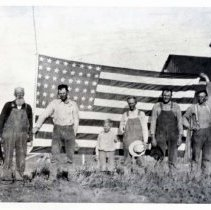 "Image of 1917 Wallowa County, Flag - On paper with photo:  ""A Flag Raising took place at the Jack Johnson horse ranch near The Buttes in Wallowa County on July 4 1917.  The flag, 8 x 10 feet, was hoisted on a 65-foot pole.  Johnson, however, deemed the flag too small and traded it for the largest size he could obtain, 10 x 15 feet.  Left to right with the flag are Jack Johnson, Philip Bunch, James Arthur Harsin, Fred A. Harsin, Amos Bunch, and James A. Davis.  Photographer was Clyde Harsin.  Jack (John William) Johnson and Jack Keeley were the first settlers on the Imnaha.  They were hunters and trappers and naturally were dubbed ""the two Jacks.""  They were both bachelors but later Mr. Johnson married Florence Mary Findley, daughter of A.B. Findley, another early settler.  Mrs. Johnson and her mother, Mrs. Findley, were the oldest white settlers (women) in the Wallowa valley.  The Findleys homesteaded at The Buttes which, for years, were called 'Findley Buttes,' after coming from Summerville where they had arrived in 1865.  The Johnsons were married on February 4, 1884 and settled on Sheep Creek.  Johnson, who came to the valley in 1878, experimented with raising sugar cane and at one time had the largest Morgan horse ranch in the United States.  He served as a scout under Gen. O. O. Howard in the Bannock War.  He was the first member initiated into the Masonic lodge at Joseph.""  Written on back:  Same info as paper, but less detailed. Also, ""Chieftan 8-22-11, Henderson, Eagle"""