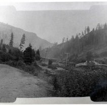 "Image of 1910+/- Oregon, Rural 1 - ""Perry area?""  There are three people standing on or near the train tracks at the right of the picture where the white rail fence is located.  Other than the tracks, this is mostly a scrubby forested area."
