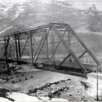 "Image of 1910+/- Oregon, Train Bridge - ""Perry area?""  This is an old train bridge running over a frozen river.  Snow is on the ground and covers the mountain in the background."