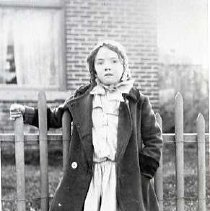 "Image of 1919 Oregon, Girl - ""Smith's Prairie School 1919""  A young girl stands in front of a short, thin rail, fence, that is outside of a brick house.  She is wearing a dark colored overcoat, a light colored bonnet and dress, and dark stockings."