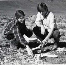 "Image of 1977 Field Trip, Desert 4 - ""October 22, 1977 - Alvord Desert Trip - Diana and Brian Dexter examine the pelvis bone from a mammal that once lived in the Alvord Desert area."""