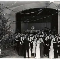 """Image of 1932 Dance, Christmas 1 - """"1932 Members of the Social Committee Dance""""  Amidst numerous, decorated, Christmas trees, including one very tall one, couples dressed in formal wear dance.  On a stage in the background, a band plays."""