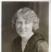 """Image of 1932 Alumni, Phyllis Munn - """"1932 - Phyllis Munn, Charter Years, c. 1929-1939""""  This is a portrait of Phyllis Munn wearing a dark colored shirt with a large, brocaded collar."""
