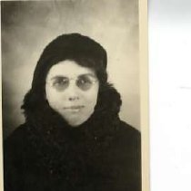"""Image of 1932 Alumni, Gladys Miller - """"1932 - Gladys Miller, Charter Years, c. 1929-1939""""  This is a portrait of Gladys Miller wearing a dark colored, cowl-necked sweater, a dark hat and round eyeglasses."""