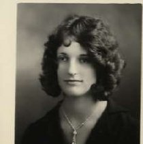 """Image of 1931 Alumni, Iris Marshall - """"1931 - Iris Marshall, Charter Years, c. 1929-1939""""  This is a portrait of Iris Marshall wearing a dark colored, v-neck, sweater, and a pendant on a chain."""