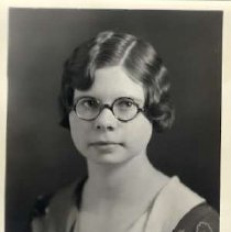 """Image of 1931 Alumni, Catherine McKinnis - """"1931 - Catherine McKinnis, Charter Years, c. 1929-1939""""  This is a portrait of Catherine McKinnis wearing a dark colored, patterned dress with a lighter colored collar.  She has a brooch at her chest, and she is also wearing oval, dark framed, eyeglasses."""