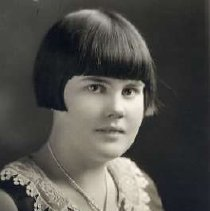 """Image of 1930 Alumni, Neelie Nelson - """"1930 - Neelie Nelson, Charter Years, c. 1929-1939""""  This is a portrait of Neelie Nelson wearing a dark colored, sleeveless sweater with a lace, v-neck collar and a knot of pearls around her neck."""