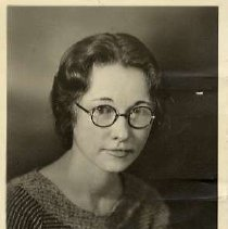 """Image of 1933 Alumni, Harriette Singleton Melfren - """"1933 - Harriette Singleton Melfren, Charter Years, c. 1929-1939""""  This is a portrait of Harriette Singleton Melfren wearing a ribbed fabric shirt with three fabric buttons at the chest and round framed, eyeglasses."""