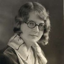 """Image of 1930 Alumni, Wilma Long - """"1930 - Wilma Long, Charter Years, c. 1929-1939""""  This is a portrait of Wilma Long wearing a dark colored shirt with a patterned scarf around her neck.  She is also wearing round, dark framed eyeglasses."""