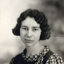 """Image of 1931 Alumni, Eleanor Meinzer - """"1931 - Eleanor Meinzer, Charter Years, c. 1929-1939""""  This is a portrait of Eleanor Meinzer wearing a dark colored, jumper over a checkered blouse with a side tie at the neckline."""