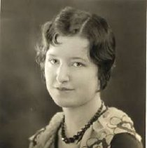 """Image of 1930 Alumni, Mary Magee - """"1930 - Mary Magee, Charter Years, c. 1929-1939""""  This is a portrait of Mary Magee wearing a dark colored, sweater with a flower patterned linen clown collar.  She also has on a string of dark beads."""