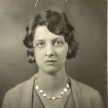 """Image of 1930 Alumni, Hilda Morrison - """"1930 - Hilda Morrison, Charter Years, c. 1929-1939""""  This is a portrait of Hilda Morrison wearing a medium colored, suit jacket over a medium colored v-neck blouse and a necklace of flowers."""