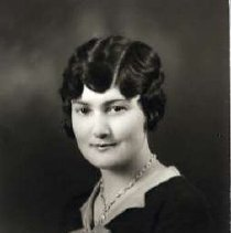 """Image of 1931 Alumni, Ida Nibeker - """"1931 - Ida Nibeker, Charter Years, c. 1929-1939""""  This is a portrait of Ida Nibeker wearing a dark colored, blouse with a lighter colored collar and bow at the chest.  She is also wearing a chain necklace."""