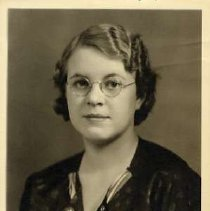 "Image of 1935 Alumni, Beth March - ""1935 - Beth March, Charter Years, c. 1929-1939""  This is a portrait of Beth March wearing a dark colored dress with polka-dots on it and a striped scarf tied in a sailor's knot at the chest.  She is also wearing  round framed eyeglasses."