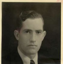 """Image of 1933 Alumni, Jerry Medcalf - """"1933 - Jerry Medcalf, Charter Years, c. 1929-1939""""  This is a portrait of Jerry Medcalf wearing a dark colored, suit over a white dress shirt and a necktie with a criss-cross pattern."""