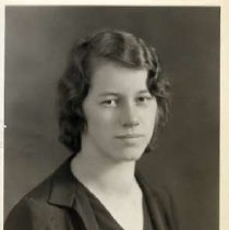 """Image of 1931 Alumni, Gertrude Moore - """"1931 - Gertrude Moore, Charter Years, c. 1929-1939""""  This is a portrait of Gertrude Moore wearing a dark colored suit jacket over a dark colored blouse with a tiny bow at the chest."""