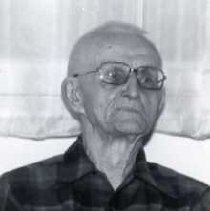 "Image of 1929 Alumni, George Overmeyer 2 - ""1986 - George Overmeyer""  This is an informal portrait of George Overmeyer wearing a dark colored, plaid shirt, and eyeglasses.  He is sitting in front of some light colored curtains."