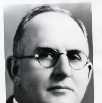 "Image of 1929-30 Employee, Harvey Inlow - ""Harvey Inlow""  This is a portrait of Harvey E. Inlow wearing a pin-striped suit blazer, a white dress shirt, a striped necktie, and round eyeglasses.