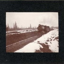 "Image of 1910+/- Oregon, Train - ""Olsen Railroad""  This is a photo of a locomotive pulling a train on tracks located in a ditch between two snow covered inclines."
