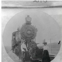 "Image of 1900+/- Oregon, Locomotive - ""Railroad""  This appears to be a photo of a photo.  A man, and two women, wearing early 1900's era clothing pose together in front of train locomotive."