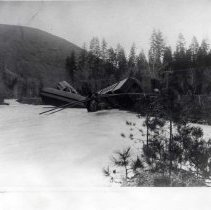 "Image of 1910+/- Oregon, Train Wreckage - ""Railroad""  This is a photo of remnants of a derailed train.  There are several passenger cars lying on their sides in the snow near the tracks."