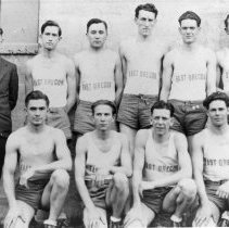 """Image of 1931 Basketball Squad - """"1931 East Oregon (Eastern Oregon Normal School) [Back row:] Coach Bob Quinn, Jerry Medcalf, Floyd Baxter, Max Horetchens, Sully, Blain Paisley. [Front row:] Cecil Posey, Earl Beery, Jack Lloyd, Garnard Coles.""""  Wearing a dark colored suit, white dress shirt, and a striped necktie, Coach Bob Quinn poses with the nine members of the East Oregon basketball squad.  They form two lines, with the back row standing and the front row kneeling."""