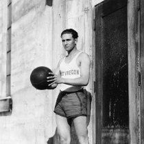 """Image of 1932 Basketball Player 3 - """"Feb. 13, 1932 - EO Normal Basketball""""  This is an informal outdoors action shot portrait of an unidentified """"East Oregon"""" basketball player.  He is wearing his uniform, and two-toned high-top tennis shoes.  He is holding a ball in both hands.  He is standing in front of a wood framed screen door."""