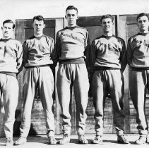 """Image of 1932 Basketball Squad 1 - """"EONS Basketball Team - Feb. 13, 1932""""  Five, tall members of the EONS, """"Mountaineers"""" basketball squad pose together in their sweatsuits.  There are wood framed, screen doors behind them."""