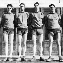 """Image of 1932 Basketball Squad 2 - """"EON Basketball Team - Feb. 13, 1932""""  Six, tall members of the EONS basketball squad pose together in two-tone sweatshirts, shorts and high-top tennis shoes.  There are wood framed, screen doors behind them."""