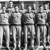 """Image of 1932 Basketball Squad 3 - """"EON Basketball Team - with Coach Quinn - Feb. 13, 1932""""  Wearing sweatsuits with """"Mountaineers"""" on the front, the twelve members of Eastern's basketball squad pose here in two rows.  The are standing on a set of steps in front of wood-framed screen doors.  The steps have some snow on them.  Dressed in a suit and necktie, Coach Bob Quinn is standing at the back right."""