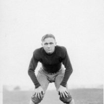 """Image of 1932 Football Player 1 - """"Harry Uhles""""  This is an informal, action shot portrait of Eastern football player, Harry Uhles.  He is wearing uniform pants, and a dark colored, long sleeved, padded, shirt."""
