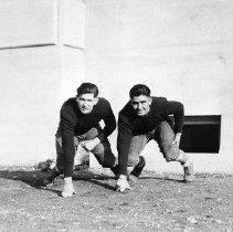 Image of 1932 Football Players - This is an informal, outdoor, portrait of two, unidentified Eastern football players.  They are  wearing their uniforms, and they are crouched in front of a newly built, Inlow Hall, as though they were on the line of scrimmage.