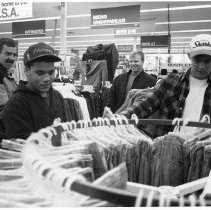 "Image of 90's Students, Shopping - ""Wal-Mart Shopping, Kirt Douglas - middle [One other name torn off.]""  Wearing ballcaps, two young men look at pants on a circular rack while two other men wait behind them.  Typical department store signs hang overhead, like ""Men's Underwear,"" ""Boys 8-18,"" ""Intimates,"" and ""Boys 4-7."""